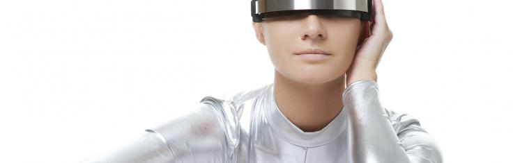 Female sat in silver suit and futurist glasses